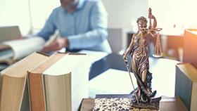 Foto: Schreibtisch mit mehreren Büchern und Figur einer Justitia