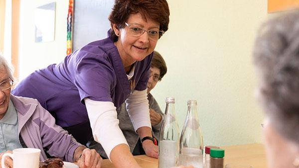 Porträt: Eine Altenpflegerin und Seniorinnen beim Tischdecken.