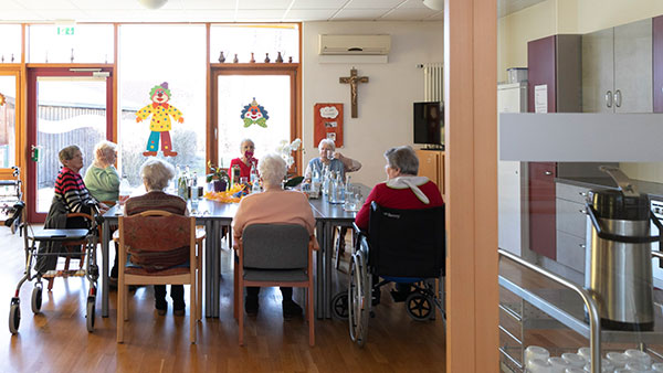 Im Esszimmer: Mehrere Senioren sitzen um einen Tisch herum.