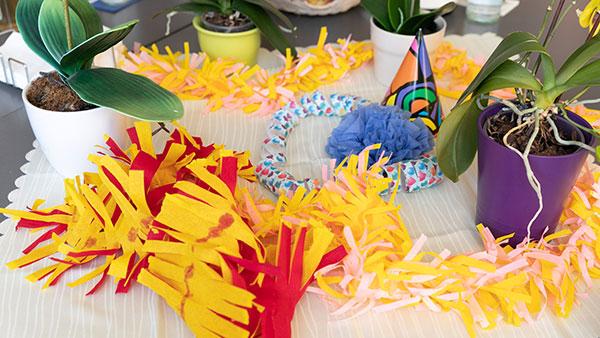 Nahaufnahme: Bunte Girlanden aus Krepppapier liegen zwischen Blumentöpfen auf einem Tisch.