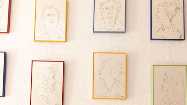 Bunte gerahmte Zeichnungen hängen an einer Wand.