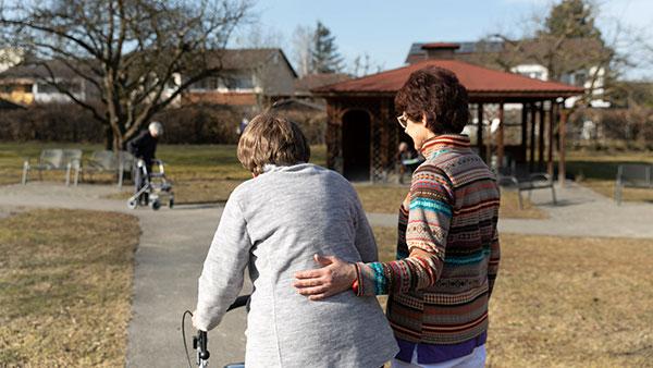 Im Garten: Gabriele S. geht mit einer Bewohnerin einen asphaltierten Weg entlang.