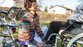 Gabriele S. kniet vor einem Rollstuhlfahrer und hält dessen linken Fuß.