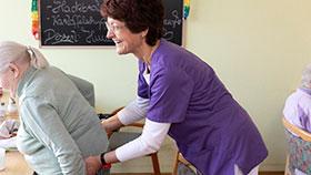 Gabriele S. hilft einer älteren Frau, sich hinzusetzen.