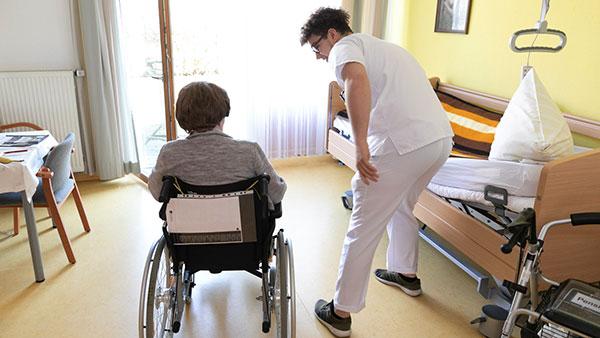 Im Bewohnerzimmer: Johannes M. wendet sich einer alten Dame im Rollstuhl zu.