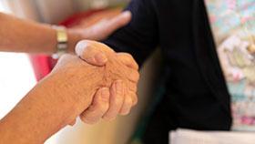 Detailaufnahme: Zwei Menschen berühren sich an Händen und Armen.