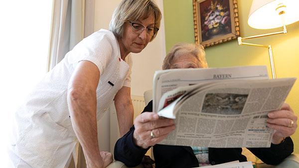 Im Bewohnerzimmer: Maria B. liest mit einer Frau Zeitung.