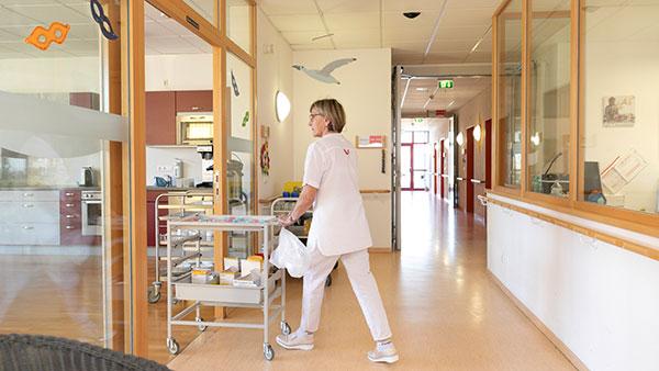 Maria B. fährt mit dem Medikamentenwagen durch einen Gang in ein Zimmer.