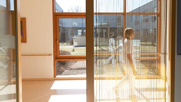 Im Altenheimflur: Maria B. geht hinter einem Vorhang einen Gang entlang.
