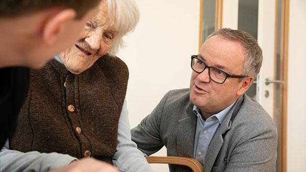 Gruppenfoto: Armin H. spricht mit einer Seniorin.