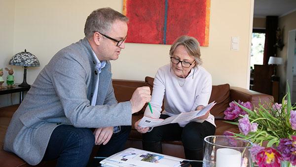 Armin H. und einer Angehörigen im Gespräch. Sie beugen sich über Informationsbroschüren.