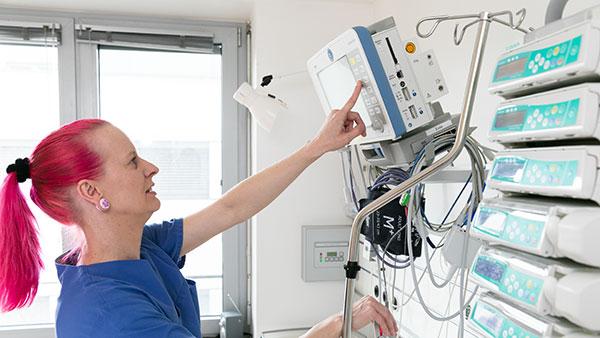Melanie S. steht vor einem großen medizinischen Gerät und bedient einen Monitor.