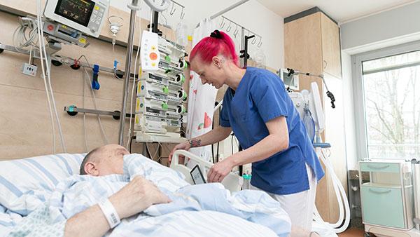 Im Krankenzimmer: Melanie S. steht am Bett eines Patienten, um den herum viele medizinische Geräte aufgebaut sind.