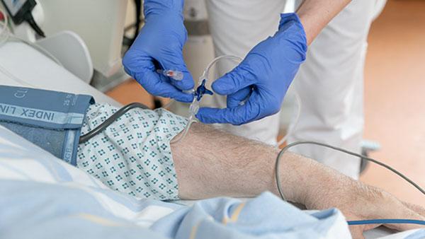 Nahaufnahme: Eine Krankenschwester legt am Patientenbett eine Infusion in den Arm eines Mannes.