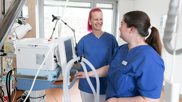 Melanie S. steht mit einer Teamkollegin an einem Beatmungsgerät und lächelt.