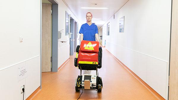 Im Krankenhausflur: Melanie S. schiebt einen Wagen mit einer roten Tasche darauf.