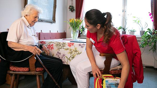 Nino A. sitzt einer Patientin gegenüber und holt etwas aus ihrem Pflegerucksack.