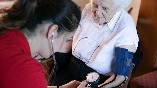 Gruppenfoto: Nino A. misst bei einer älteren Dame den Blutdruck.