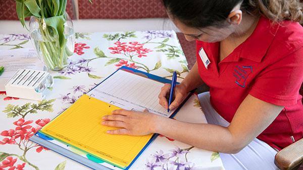 Nino A. sitzt am Tisch und schreibt etwas in eine Pflegemappe.