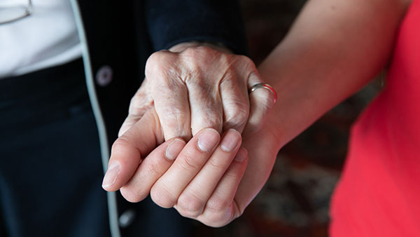 Nahaufnahme: Zwei Hände, die einer älteren und die einer jüngeren Frau, halten einander vertrauensvoll.