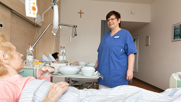 Petra E. steht bei einer Patientin am Bett.