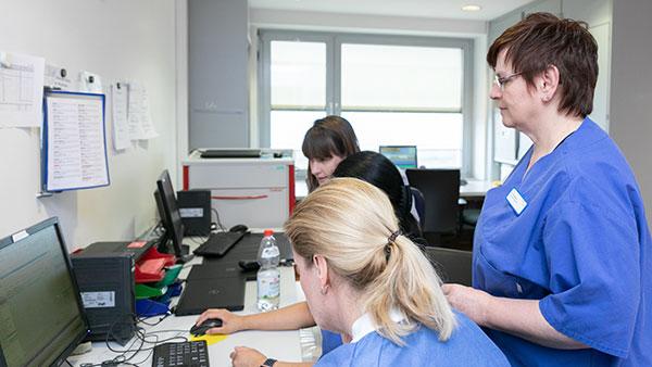 Petra E. steht zwischen mehreren Kolleginnen, die an einem Schreibtisch sitzen.