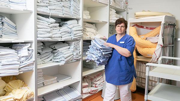 In der Wäschekammer: Petra E. trägt einen Stapel Kleider.