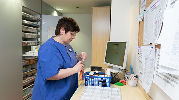Petra E. hält eine Medikamentenschachtel in der Hand.