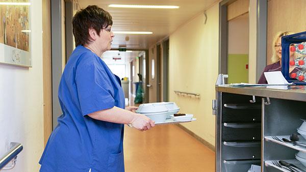 Im Krankenhausgang: Petra E. trägt ein Tablett mit Essen.