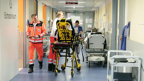 Übersichtsaufnahme: Sanitäter stehen in einem Krankenhausgang neben einer Krankentrage.