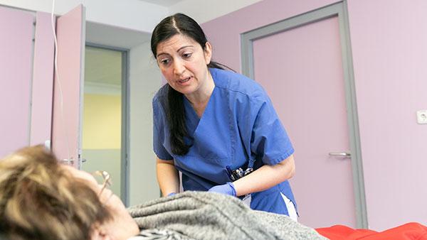 Im Behandlungsraum: Senay C. beugt sich über eine liegende ältere Dame.