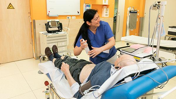 Übersichtsaufnahme: Senay C. steht über einen Mann gebeugt, der auf einer Behandlungsliege liegt.