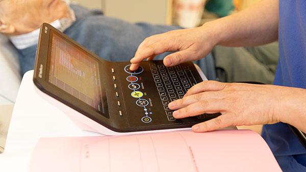 Nahaufnahme: Hände tippen auf einem kleinen Computer.