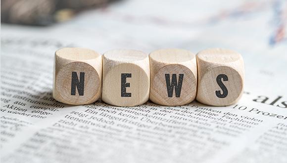 Buchstaben-Würfel News auf einer Zeitungsseite